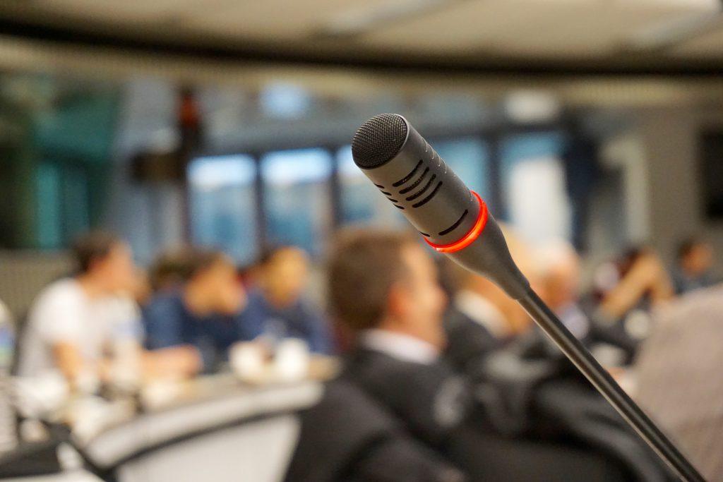 Mikrofon na mównicy. W tle tłum ludzi
