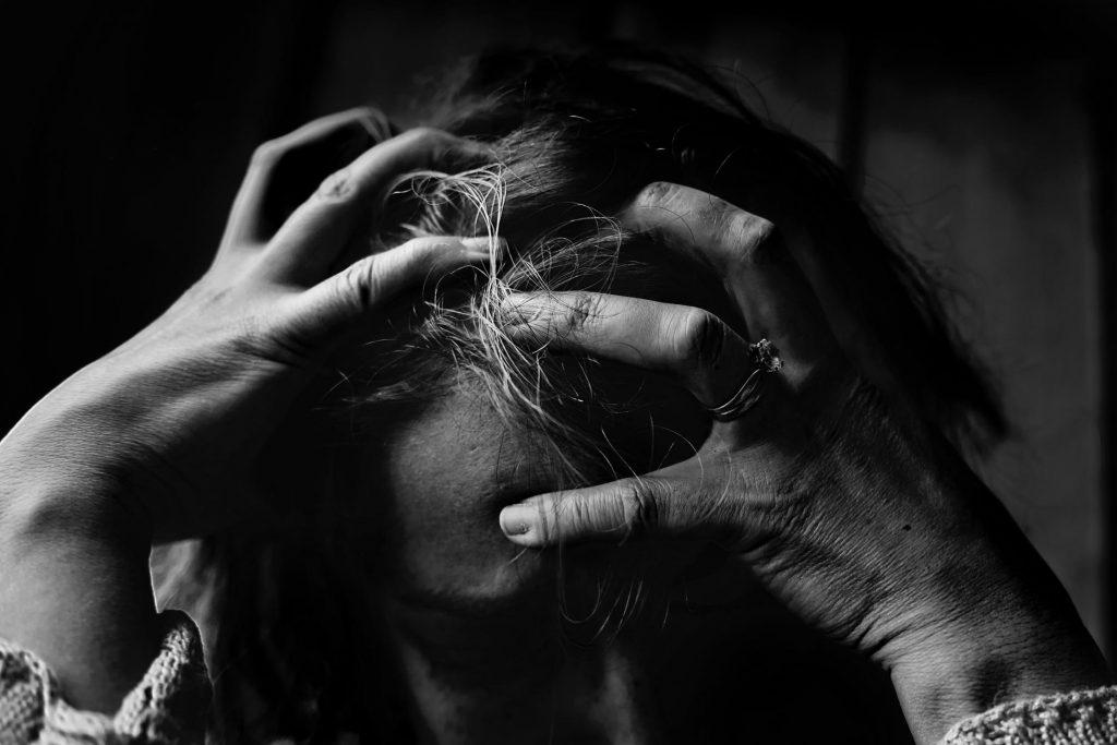 Kobieta trzymajaca się za głowę dłońmi