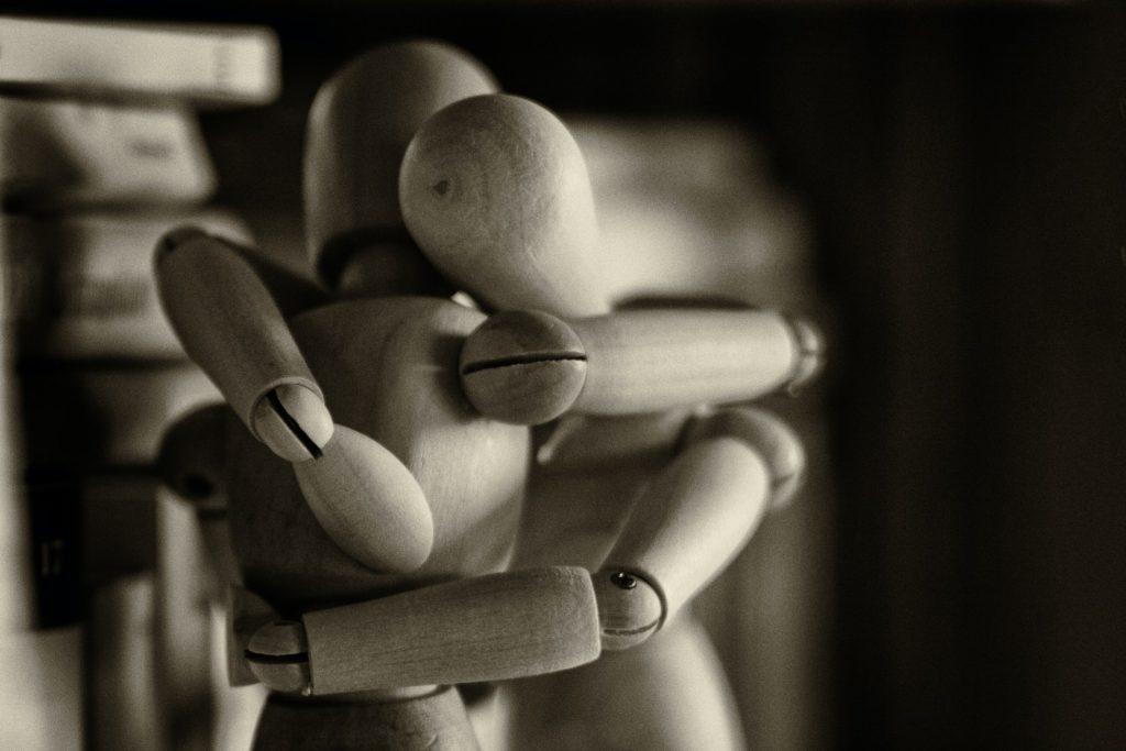 Dwie przytulajace się drewniane figurki