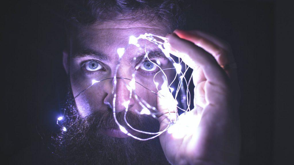 Mężczyzna trzymajacy w dłoni świetlny sznurek