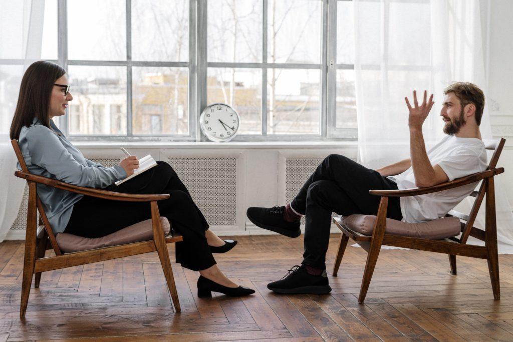 Kobieta i mężczyzna siedza na przeciwko siebie