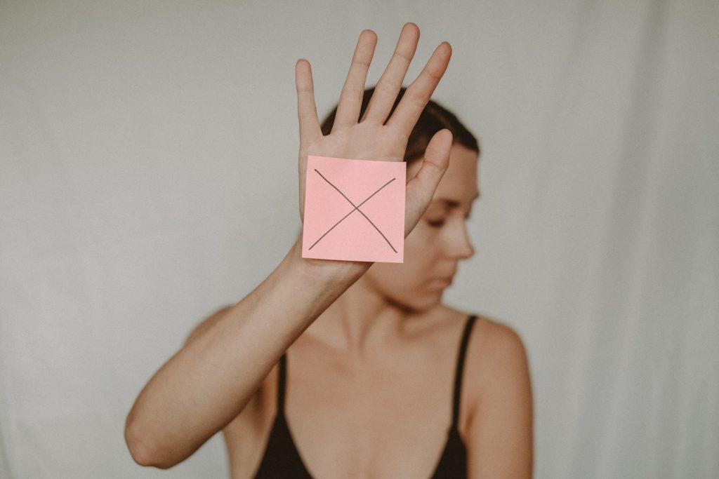 Kobieta zasłania swoją twrz dłonią na której ma karkę